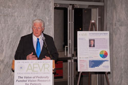 Cong. Moran spoke about the importance of vision research funding at the NEI and DOD, which he has championed as a Congressional appropriator. He is flanked by a poster of the front page of AEVR's 20th  anniversary brochure The Value of Federally Funded Vision Research-NEI.