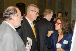 Congressman Randy Hultgren (R-IL), center, speaks with Dimitra Skondra, MD, PhD (University of Chicago), right, as Dr. Steinmetz listens